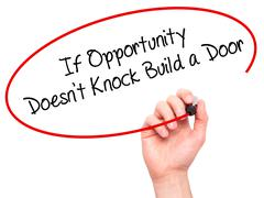 Man Hand writing If Opportunity Doesn't Knock Build a Door with black marker  - stock photo