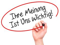 Man Hand writing Ihre Meinung Ist Uns Wichtig! (Your Opinion is Important to  - stock photo