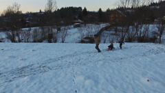 Father pulling slade with kids having fun in winter, aerial view Stock Footage