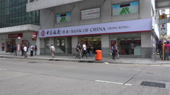 People walk past Bank of China branch office in Hong Kong Stock Footage