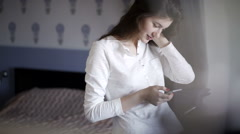 Beautiful young girl writes a message. She dreams and smiles Stock Footage