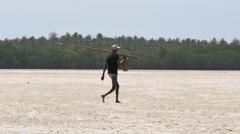 Pan of fisherman walking through the Mida Creek - stock footage
