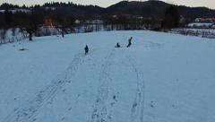 Father pulling slade, kids having fun in winter, aerial view Stock Footage