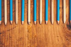 Blue and brown lined up pencils on rustic wooden table Stock Photos