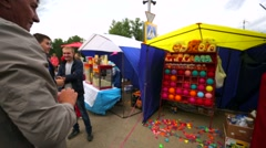 Man throws dart to balloon for fun during Festival of small nations. Stock Footage