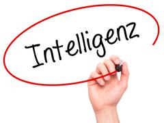 Man Hand writing Intelligenz (Intelligence in German) with black marker on vi - stock photo