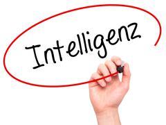 Man Hand writing Intelligenz (Intelligence in German) with black marker on vi - stock photo