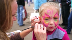 Little girl gets her face painted like a butterfly by face painting artist. Stock Footage