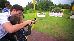 boy teaches the younger sister to shoot a bow. - stock footage