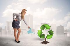 Business woman watering green recycle sign tree on city background - stock photo