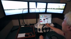 Man steer wheel of a boat simulator at  water rescue station. Stock Footage