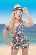 Beautiful young pretty blonde woman in sunglasses and  summer hat by the sea. Stock Photos