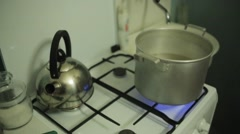 Man hand cover saucepan with water on gas stove by old round drum plate. Kettle Stock Footage