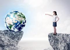 Businesswoman on rock mountain with a globe Kuvituskuvat