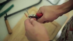 Man hands hardly cut, snip long wire by red pliers. Close Up Stock Footage