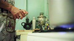 Man hands hardly cut, snip long wire by red pliers on kitchen. Burning gas stove Stock Footage