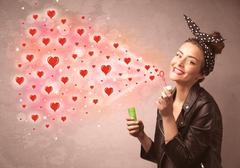 Pretty young girl blowing red heart symbols Stock Photos