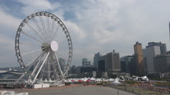 A large ferris wheel in front of the Hong Kong skyline Stock Footage