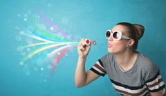 Stock Photo of Beautiful girl blowing abstract colorful bubbles and lines