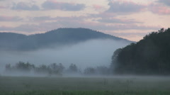Foggy morning, meadow, forest against the backdrop of the mountains, cloudy sky Stock Footage