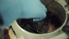 Man in gloves got many wires from saucepan and put it in bank. Art house cooking Stock Footage