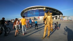 Street performer with a head on a stick greets tourists Stock Footage