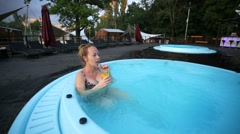 Young woman relaxing in hot tub, outdoors. Stock Footage