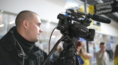 Stock Video Footage of Videographer with a Camcorder at the Scene removes a Report at the Mall