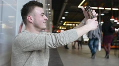 A man with Smartphone mobile cell phone in a hand Makes Selfie Photos Stock Footage