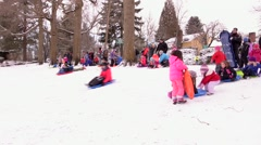 Group of kids sliding down a snowy hill within a park Stock Footage