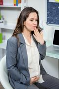 Stock Photo of Pregnant businesswoman getting morning sickness