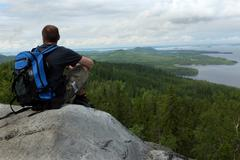 tourist sits on a cliff in the national park Koli, Finland - stock photo