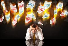 Depressed businessman sitting under burning tax and bill papers Stock Photos