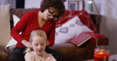 4K Babysitter at home with little girl, styling her hair - stock footage