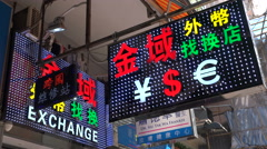 Neon advertising billboard displays currency exchange in Hong Kong China Asia Stock Footage