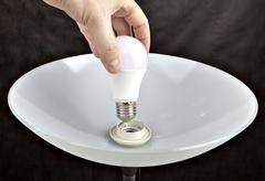 Hand replacing led light bulb lamp Kuvituskuvat
