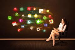 Business woman sitting in office chair with tablet and colorful app icons Stock Photos