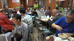 People eat lunch in a popular local restaurant in Hong Kong Stock Footage