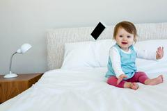 Adorable baby giggling and throwing a phone Stock Photos