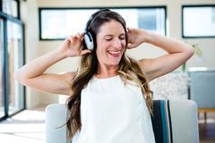 Smiling woman listening to music on her headphones Kuvituskuvat