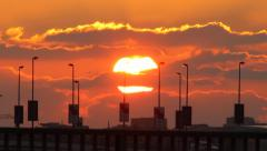 Large sun disk behind clouds, sunset time. Telephoto view, road traffic on fore Stock Footage