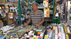 Chinese market vendor sells household appliances, power plugs, batteries Stock Footage