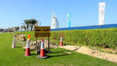 Deep excavation sign and warning cones around ditch along grass lawn Stock Footage
