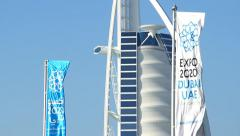 Blue and white banner about Expo 2020 flutter on wind against Burj Al Arab hotel Stock Footage