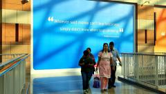Indian family go at shopping complex against banner with curious citation - stock footage