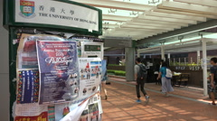 Students walk past a notice board for activities at the Hong Kong University Stock Footage