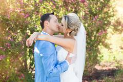 Wedding newlyweds kiss on a sunny day Stock Photos