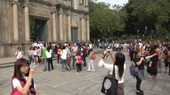 Chinese tourists take photos and selfies at St Paul's church in Macau Stock Footage