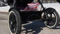 A low shot mother pushing baby in stroller - stock footage