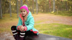 Smiling little girl in blue jacket in autumn park Stock Footage